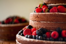 Three tiered chocolate cake with white vanilla cream cheese icing and summer berries.