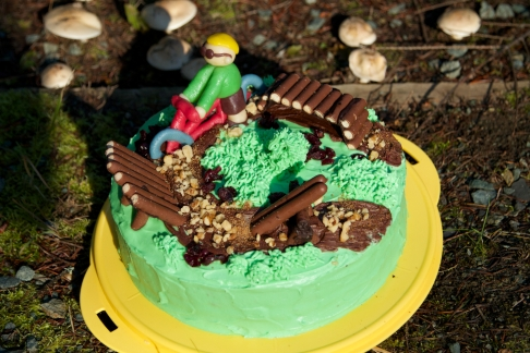 Carrot cake with green cream cheese icing, Cadbury's Chocolate Fingers and nuts. With marzipan biker.