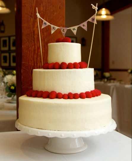 Three tiered vanilla sponge cake with vanilla buttercream icing and raspberries.
