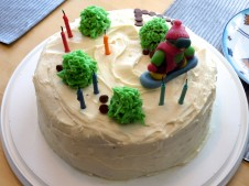chocolate cake with cream cheese icing for the snow, chocolate chips for the rocks and strawberries and green icing for the trees and a snowboarder made of marzipan.