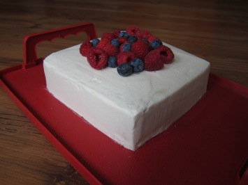 Vanilla sponge with raspberry jam in the middle, buttercream icing and raspberries and blueberries.
