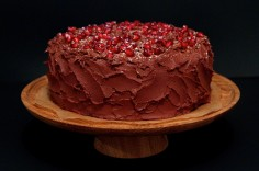 Chocolate sponge with a chocolate ganache icing with pomegranate seeds and chocolate curls on top.