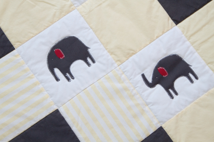 Close up of the 2 kinds of elephant details on the quilt. Yellow, white and grey elephant quilt. Made from up-cycled fabric.