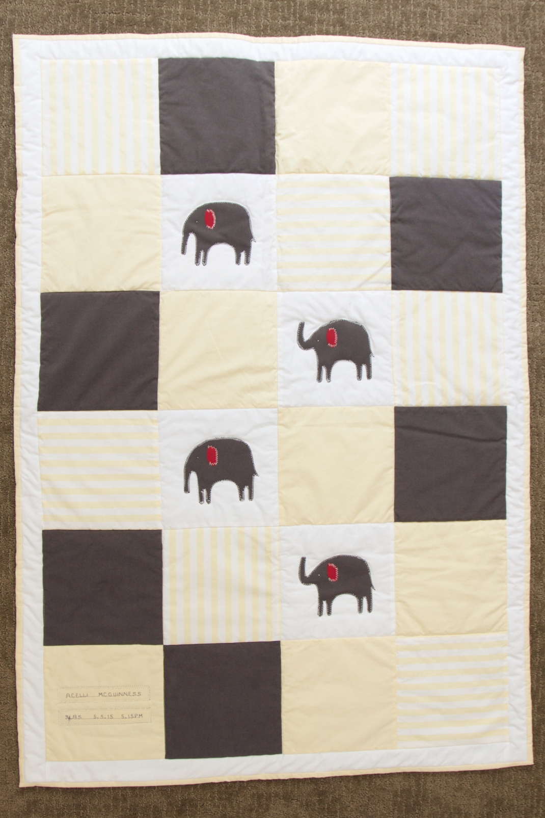 The front of the quilt. Yellow, white and grey elephant quilt with white stitching. Made from up-cycled fabric.