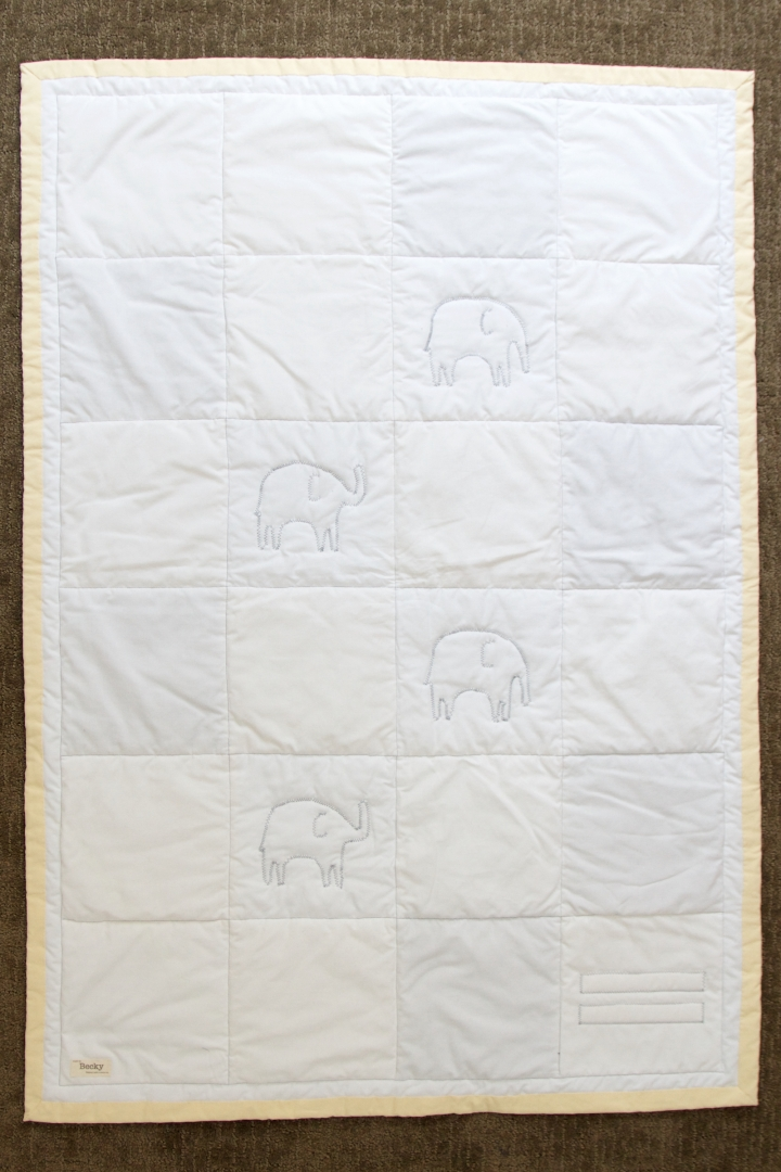 The back of the elephant quilt. White fabric with grey stitching. Made from up-cycled fabric.