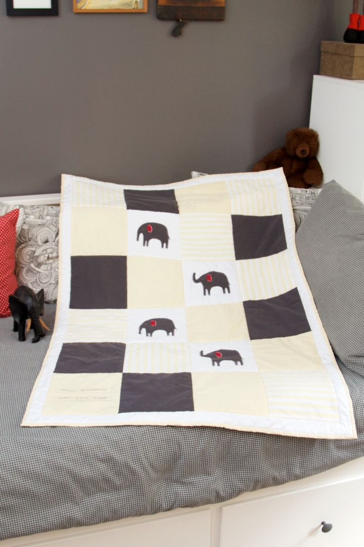 The finished quilt. Yellow, white and grey elephant quilt with white and grey stitching. Made from up-cycled fabric.