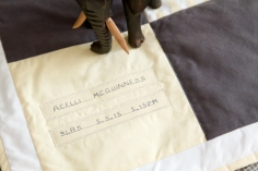 Acelli McGuinness' quilt, personalised with her name and birth detail. Grey stitching on yellow fabric. Made from up-cycled fabric.