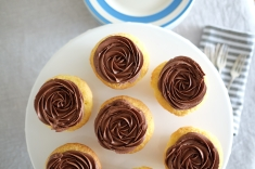 Vanilla cupcakes with rose piped chocolate buttercream icing.