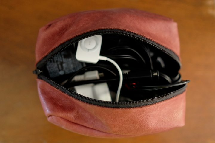 Open top of leather bag with wires inside.