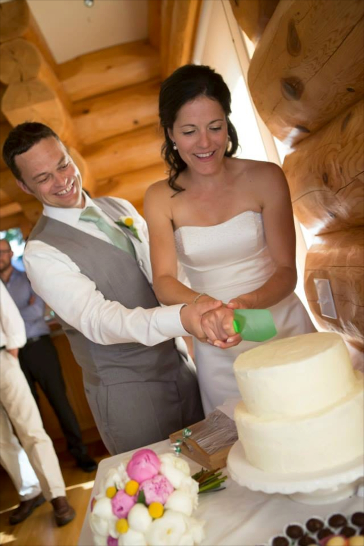Maz and Tim cutting their green wedding cake with their green knife. Green vanilla sponge with lemon buttercream icing.