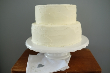 Two tiered green vanilla sponge cake with lemon buttercream icing and napkins.