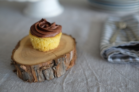 Mini vanilla cupcakes with rose piped chocolate buttercream icing.